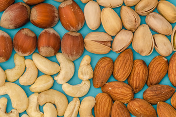 Group of different nuts isolated on blue