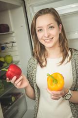 Junge Frau nimmt Obst und Gemüse aus dem Kühlschrank raus
