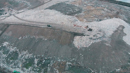 Aerial Shot Landfill with Working Trucks and Tractor, top view