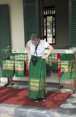 Tourist borrows a sarong before entering a religious temple