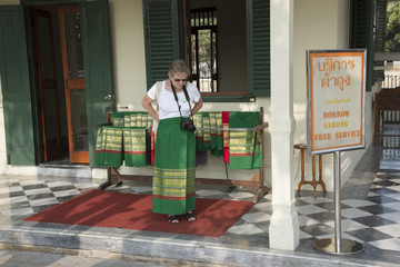 Tourist fastens a sarong before entering a Thai temple