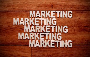la parola marketing ripetuta sulla tavola di legno