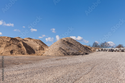 Piles of Gravel at Construction Site under Bright Blue Sky