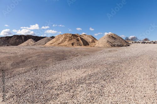 Piles of Gravel at Construction Site under Bright Blue Sky - 81082731