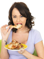 Young Woman Eating Cold Cooked Chicken Legs