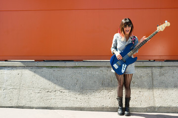 Laughing woman holding blue bass guitar outside