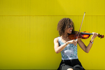 Smiling Young woman playing violin outside