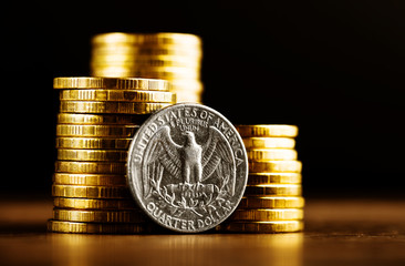 us quarter dollar coin and gold money on the desk