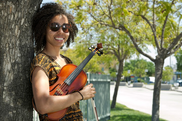 African American woman holding violin and leaning against tree