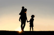 Silhouette of Mother and Young Children Holding Hands at Sunset - 81086579