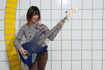 Female musician playing guitar in subway with tongue out