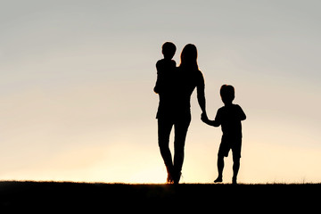 Silhouette of Walking Mother and Young Children Holding Hands at