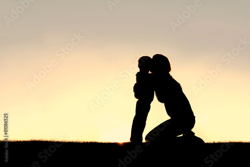 Silhouette of Young Mother Hugging Toddler Son at Sunset - 81086525