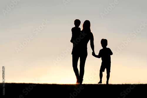 Silhouette of Walking Mother and Young Children Holding Hands at - 81086529