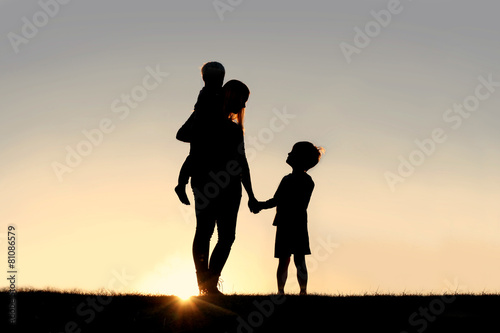Leinwanddruck Bild Silhouette of Mother and Young Children Holding Hands at Sunset
