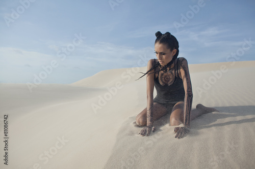 young pretty woman in white sand dunes like a goddes of darkness - 81086742