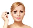 Beautiful woman applying mascara on her eyelashes, isolated