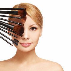 Beautiful woman with makeup brushes near attractive face