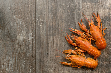 Three red crayfishes on old wooden table