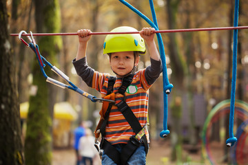 Cute small boy enjoying a sunny day in a climbing adventure acti