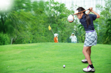 Little asian girl playing golf