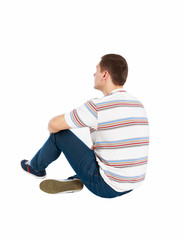 Back view of seated handsome man in t-shirt and jeans looking up