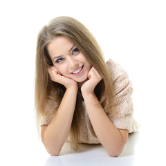 Beautiful happy blond girl lying and looking at camera. Isolated