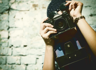 urban girl has fun with vintage photo camera outdoor near grunge