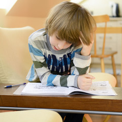 Cute little boy doing his homework.