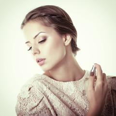Girl with perfume, young beautiful woman holding bottle of perfu
