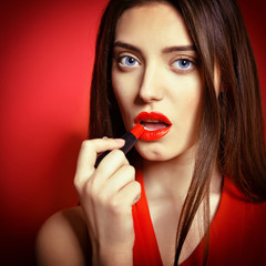 Beautiful young woman applying red lipstick on her lips.