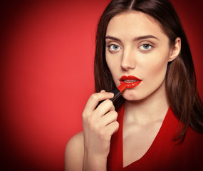 Beautiful young woman applying red lipstick on her lips. Toned.
