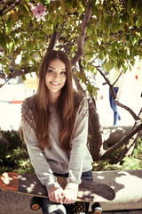 Beautiful teen girl with skateboard. Urban outdoors, teenager's