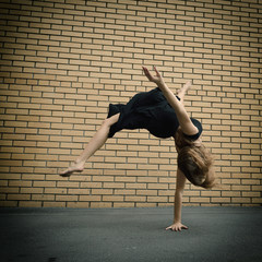 Attractive teen girl dancing outdoor against brics wall. Toned.