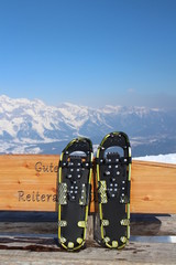Snowshoe on bench with Alps
