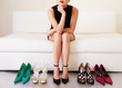 Woman thinking on sofa with many shoes.Shopping - 81096506