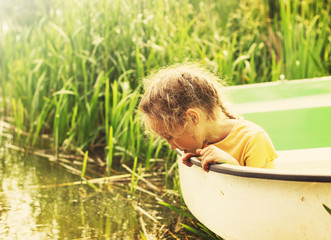 Toned Portrait of Little girl sitting at the boat by a river