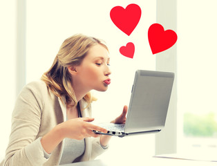 woman sending kisses with laptop computer