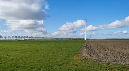 Wind turbine in a plowed field in spring