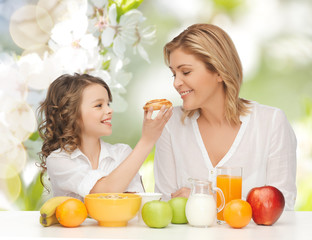 happy mother and daughter eating breakfast