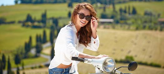 Young beautiful italian woman sitting on a italian scooter in tu