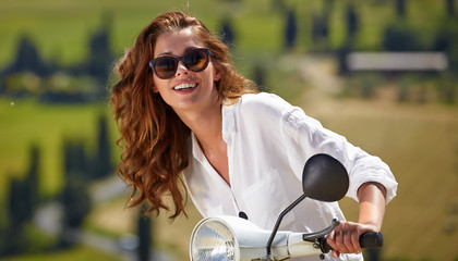 Young beautiful italian woman sitting on a italian scooter in It