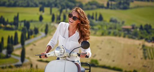 Young beautiful italian woman sitting on a italian scooter in It