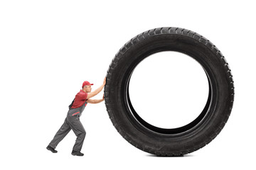 Mechanic in a gray jumpsuit pushing a giant black tire