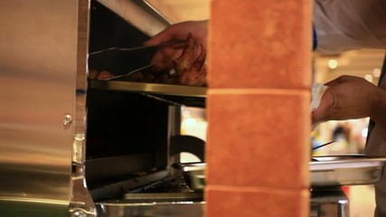 Chef putting meat into oven in the kitchen. HD. 1920x1080