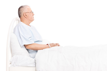 Senior patient lying in a bed and looking around