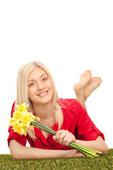 Woman holding a bunch of tulips and lying on grass