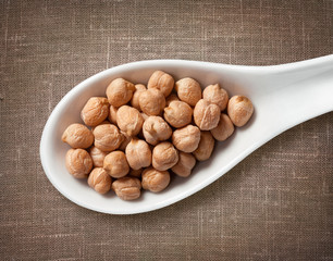 Chickpea in white porcelain spoon on burlap sackcloth background