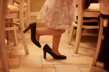 Legs of a girl playing with mothers shoes