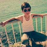 Niño con gafas de sol junto al mar